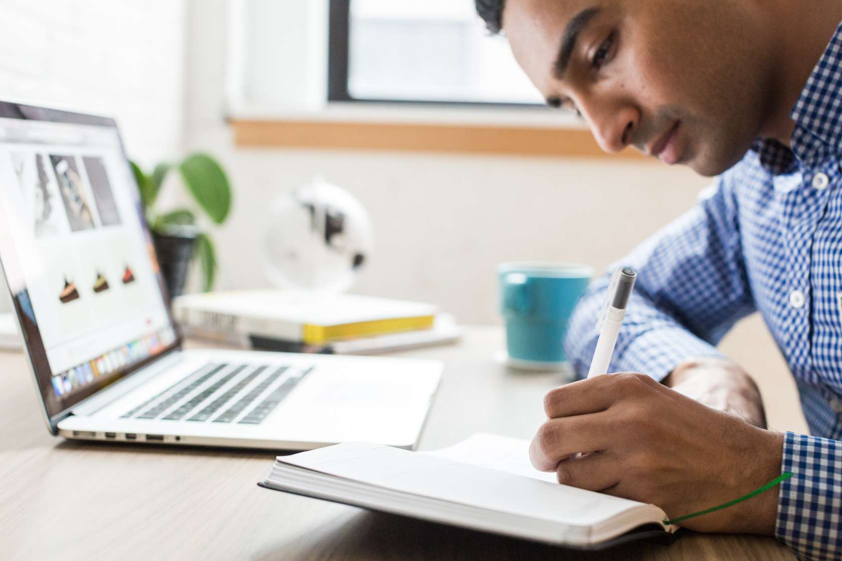 Man taking notes with laptop open